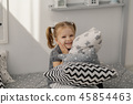 Little beautiful girl with light pillows in a cozy 45854463