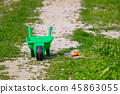 Toy wheelbarrow with shovel on grass, abandoned toy 45863055