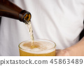 Hands man pouring beer from bottle into glass 45863489