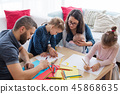 A portrait of young family with small children around table indoors, drawing. 45868635