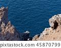 Rock coast against blue water 45870799
