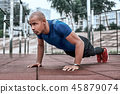 African man is doing plank at open air gym near the park 45879074