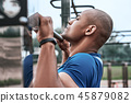 An african man is pulling up at open air gym. Close-up, side view 45879082