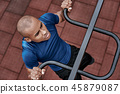 An african man is pulling up at open air gym. Close-up, top view 45879087