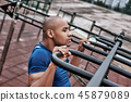 An african man is pulling up at open air gym. Close-up, side view 45879089