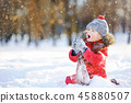 Little boy in red clothes having fun with snow 45880507