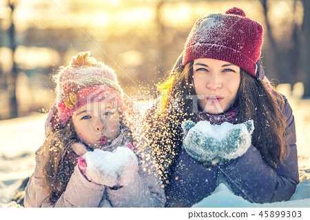 Mother and daughter playing in winter park 45899303