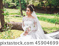Beautiful happy bride with bouquet of flowers in park 45904699