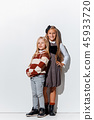 The portrait of cute little girls in stylish jeans clothes looking at camera at studio 45933720