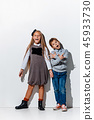 The portrait of cute little boy and girl in stylish jeans clothes looking at camera at studio 45933730