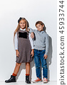 The portrait of cute little boy and girl in stylish jeans clothes looking at camera at studio 45933744