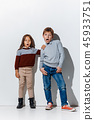 The portrait of cute little boy and girl in stylish jeans clothes looking at camera at studio 45933751