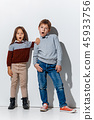 The portrait of cute little boy and girl in stylish jeans clothes looking at camera at studio 45933756