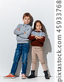 The portrait of cute little boy and girl in stylish jeans clothes looking at camera at studio 45933768