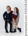 The portrait of cute little boy and girl in stylish jeans clothes looking at camera at studio 45933810