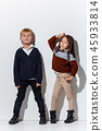 The portrait of cute little boy and girl in stylish jeans clothes looking at camera at studio 45933814