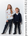The portrait of cute little boy and girl in stylish jeans clothes looking at camera at studio 45933821