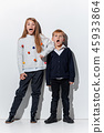 The portrait of cute little boy and girl in stylish jeans clothes looking at camera at studio 45933864