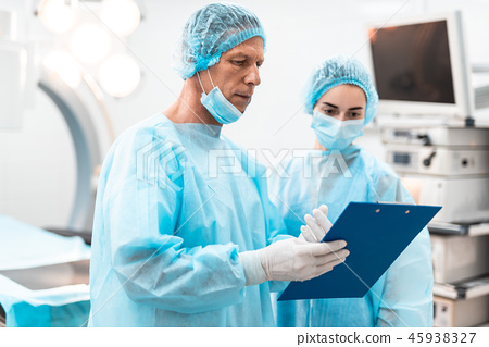 Calm doctor holding blue clipboard and talking to colleague 45938327