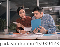 Modern smart freelancers holding blue tablet while working 45939423