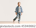 The portrait of cute little boy in stylish jeans clothes looking at camera at studio 45940662
