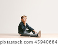 The portrait of cute little boy in stylish jeans clothes looking at camera at studio 45940664