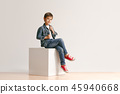 The portrait of cute little boy in stylish jeans clothes looking at camera at studio 45940668