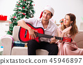 Young couple playing guitar at christmas 45946897