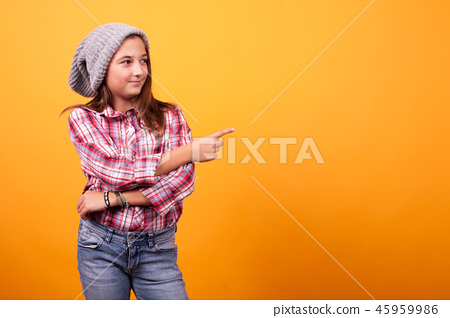 Little girl pointing in studio on yellow background. 45959986