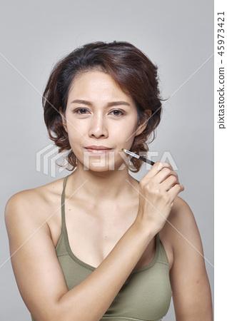Closeup beautiful woman with eyebrow brush tool on gray 45973421