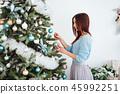 Girl dresses up Christmas tree 45992251