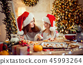 Merry Christmas and Happy Holidays. Mother and daughter cooking Christmas cookies. 45993264