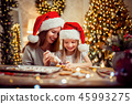 Merry Christmas and Happy Holidays. Mother and daughter cooking Christmas cookies. 45993275