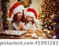 Merry Christmas and Happy Holidays. Mother and daughter cooking Christmas cookies. 45993283