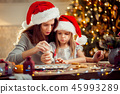 Merry Christmas and Happy Holidays. Mother and daughter cooking Christmas cookies. 45993289