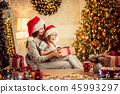 a happy family mother and child pack Christmas gifts 45993297