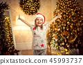 happy cheerful girl in christmas pajamas, santa helper hat raised her hands up. 45993737
