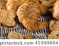 Croissant on rattan mat with other bakery goods 45999664