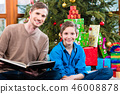 Daddy reading out from book for kid under X-mas tree 46008878