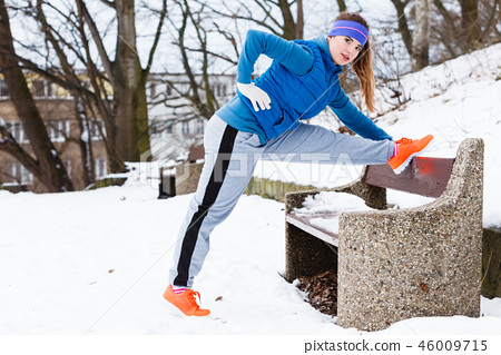 Woman wearing sportswear exercising outside during winter 46009715