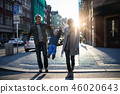 A small toddler boy with parents crossing a road outdoors in city at sunset. 46020643