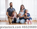A portrait of young family with small children indoors, baby and dolls in carriers. 46020689