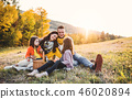 A young family with two small children having picnic in autumn nature at sunset. 46020894