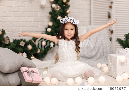 child girl makes paper snowflakes for decoration Christmas tree 46021077