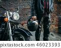 Biker in leather jacket with helmet in hand 46023393
