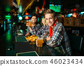 Fans with glasses of beer at counter in sports bar 46023434