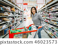 Young woman with cart full of goods in supermarket 46023573
