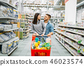 Young woman with cart full of goods in supermarket 46023574