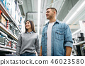 Couple looking on shelf with electric ovens 46023580
