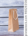 Brown paper shopping bag with white handles. 46026356